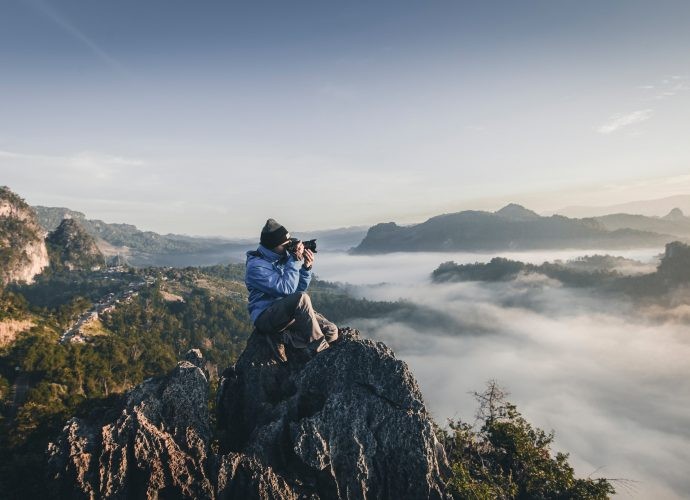 homme en haut d'une montagne prenant des photos